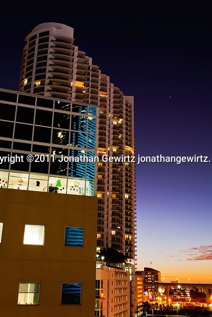 Twilight view of office and condo buildings near Miami's downtown, showing Christmas decorations and colorful reflections.