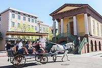 Tourists take a horse-drawn carriage tour past the historic Charleston City Market in Charleston, South Carolina.