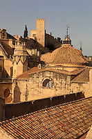 Buttresses of the Cathedral of Saint Mary of Tortosa, and Castle of Sant Joan or La Suda, Tortosa, Tarragona, Spain. The Catalan Gothic cathedral, on the left, was begun in 1347 and consecrated 1597. The 10th century Castle of Sant Joan was built by Muslim Caliph Abd ar-Rahman III. It was conquered in 1148 and became residence of the Montcada and Knights Templar, then a royal mansion from the 13th century. Here the cathedral and castle are seen over the rooftops of the old town of Tortosa. Picture by Manuel Cohen