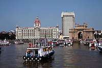 Tourist ferries pass in front of the Taj hotel and Gateway to India monument that faces the Arabian sea on the Marine Drive in Mumbai, India. Photo by Suzanne Lee
