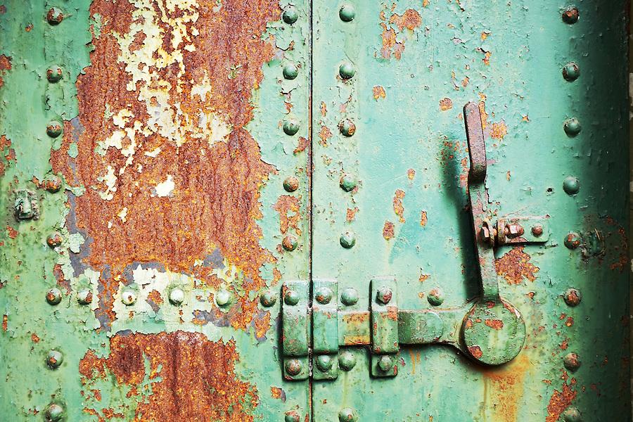 Closed rusty green steel door in concrete bunker, Artillery Hill, Fort Worden State Park, Port Townsend, Washington, USA