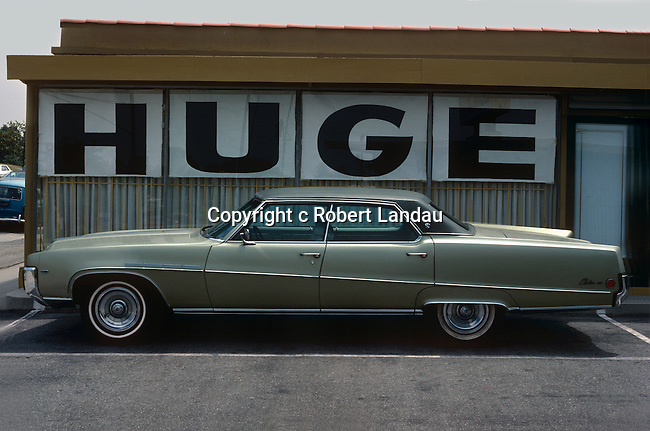 Car parked below Huge sign in Los Angeles, CA June 1977