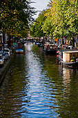 Amsterdam, Holland. Looking down the canal, trees, houseboats and people make this area a place to visit.