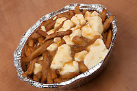 A poutine over a wood table. Poutine is a French Canadian dish consisting of French fries topped with fresh cheese curds and covered with hot gravy.