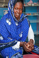 Jambiani, Zanzibar, Tanzania.  Woman Making Coconut Milk.  She wears a nose-pin in her left nostril.  Her outer garment is of kitenge cloth.