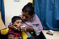 Razia Shabnam (in orange) shares a chai (tea) with her son Saihaan, while on a train to referee an all-India invitational boxing competition in the neighbouring town of Burnpur, Calcutta, West Bengal, India. Razia Shabnam, 28, was one of the first women boxers in Kolkata. She was also the first woman in her community to go to college. She is now a coach and one of only three international female boxing referees in India. Photo by Suzanne Lee for Panos London