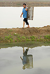 Nguyen Xuan Hien, who lost a leg to a landmine, walks home from his shrimp pond in Bo Trach, Vietnam.