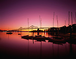 San Francisco Oakland Bay bridge at sunrise with street lights and bridge lights, and small marina with sailboats silhouetted San Francisco, California USA