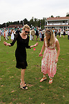 Young women tread in diviots during break in play. The Guards Polo Club, Windsor Great Park. England.