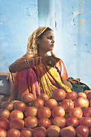 A woman sits by her fruit stall, Pushkar, Rajasthan, India. The small town attracts tens of thousands of pilgrims during 'Karthik Purnima' a sacred hindu festival. During the festivities, a popular cattle fair and camel race takes place in the Thar desert.