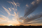 Algodones Dunes, Glamis, California; the setting sun lights up the clouds over the silhouette sand dunes