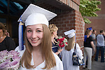 A young woman is photographed just after her High School Graduation ceremony.