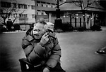Battered homeless man smokes in a park near the Sumida River, Asakusa, Tokyo, Japan.