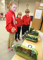 NWA Democrat-Gazette/ANDY SHUPE<br /> Izzy Kenney f(from left), 11, a sixth-grader at St. Joseph Catholic School in Fayetteville, shows a series of planters Thursday, Feb. 9, 2017, to Fletcher Schmidt, 1, and Hayden Beckerdite, 9, both fourth-graders, as she explains her study of the effect of plants on erosion while participating in the school's science fair at the school in Fayetteville. Sixth- through eighth-graders at the school took part in the fair with a chance to compete in the Northwest Arkansas Regional Science and Engineering Fair March 3 at the University of Arkansas.