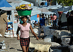 "Carrying bananas on her head, a woman walks through the largest ""tent city"" of Haitian earthquake survivors, located on a former nine-hole golf course in Port-au-Prince. The Petionville Club is host to more than 44,000 people.."