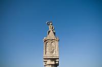 Stone watchman on medieval stone bridge crossing Danube river, Regensburg, Germany