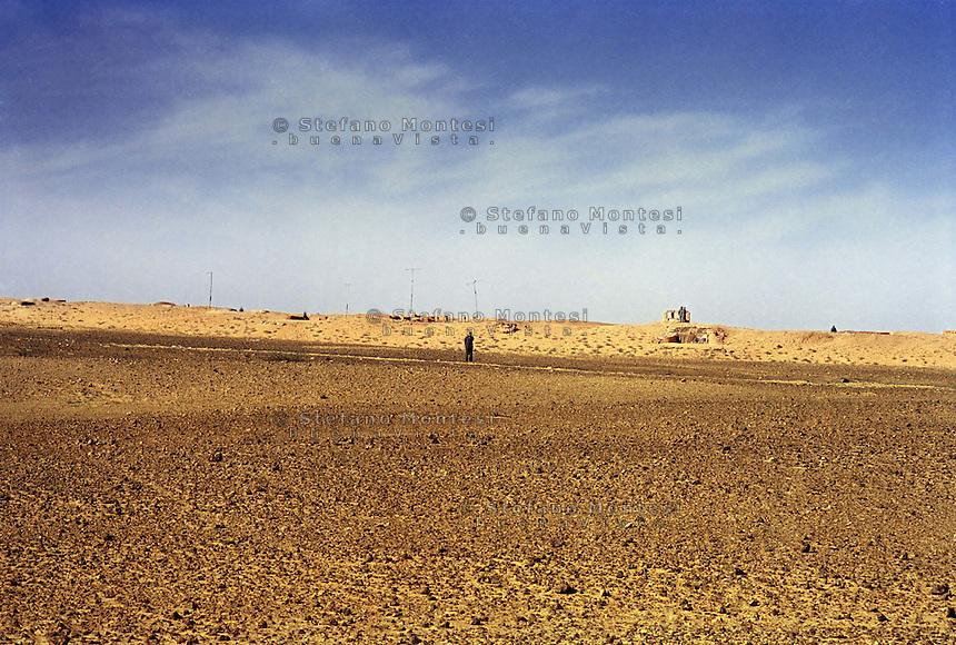 """Sahara Occidentale.Soldati dell'Esercito del Marocco  di guardia  sul muro.Il muro marocchino o muro del Sahara Occidentale è un insieme di otto muri difensivi con una lunghezza superiore a 2.720 km costruito dal Marocco nel Sahara Occidentale. È una zona militare con bunker, fossati e campi minati, edificato con l'obiettivo di proteggere il territorio occupato dal Marocco dalle incursioni del Fronte Polisario..Army soldiers guarding the wall of Morocco.The Berm of Western Sahara (also known as the Moroccan Wall) is an approximately 2,700 km-long defensive structure, mostly a sand wall (or """"berm""""), running through Western Sahara and the southeastern portion of Morocco. It acts as a separation barrier between the Moroccan-controlled areas and the Polisario-controlled section of the territory that lies along its eastern and southern border."""