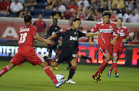AC Milan midfielder Ronaldinho (80) attempts a shot in between Chicago Fire midfielders Mike Banner (18) and Baggio Husidic (9).  AC Milan defeated the Chicago Fire 1-0 at Toyota Park in Bridgeview, IL on May 30, 2010.
