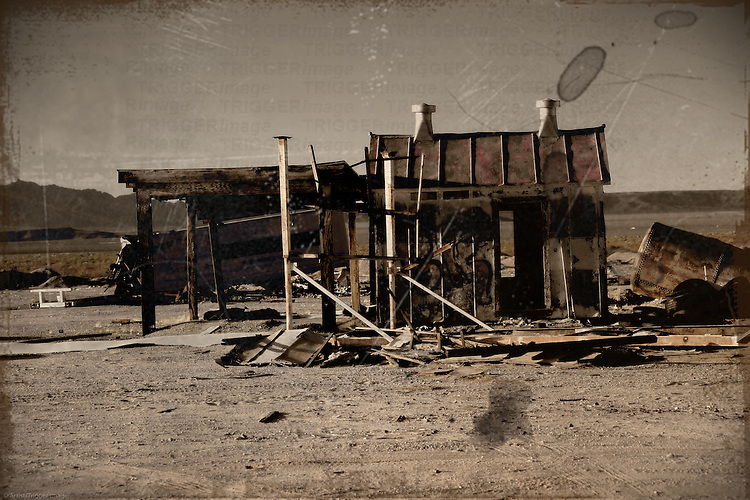 Abandoned wooden cottage, camping trailers and rusted water tank in the desert.