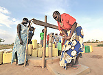 Margaret Dure (right) pumps water from a well constructed by the United Methodist Committee on Relief (UMCOR) in the Southern Sudanese town of Yei.