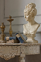 A restored Napoleon III console table has been given an 18th century wooden frieze and displays a candlestick and some antique books with a contemporary terracotta bust which has been painted to be more in harmony with the still life