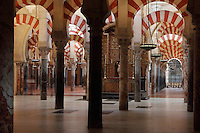 The hypostyle prayer hall, area built in the 10th century under Al-Hakam II, 961-976, in the Cathedral-Great Mosque of Cordoba, in Cordoba, Andalusia, Southern Spain. The hall is filled with rows of columns topped with double arches in stripes of red brick and white stone. The first church built here by the Visigoths in the 7th century was split in half by the Moors, becoming half church, half mosque. In 784, the Great Mosque of Cordoba was begun in its place and developed over 200 years, but in 1236 it was converted into a catholic church, with a Renaissance cathedral nave built in the 16th century. The historic centre of Cordoba is listed as a UNESCO World Heritage Site. Picture by Manuel Cohen