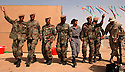 """Soldiers from the first battalion of New Iraqi Army (NIA) soldiers dance """"choby"""" style with one of their trainers (grey uniform) and an American soldier (r) to celebrate their October 4, 2003 graduation at the Iraqi Army training center in Kirkush, Iraq."""