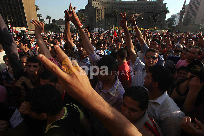 Protesters wave Egypt's flags during a demonstration at Tahrir square in Cairo, against the verdict for deposed leader Hosni Mubarak June 4, 2012. Egyptian pro-democracy campaigners called on Sunday for a new uprising, saying justice was not served by the trial of Mubarak and others blamed for the killing of protesters during the street revolt that ended his three-decade rule. Photo by Ashraf Amra
