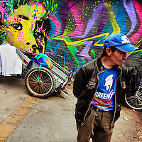 A Colombian street vendor stands in front of a graffiti artwork, created by an artist named Stinkfish, in the center of Bogotá, Colombia, 21 February, 2016. A social environment full of violence and inequality (making the street art an authentic form of expression), with a surprisingly liberal approach to the street art from Bogotá authorities, have given a rise to one of the most exciting and unique urban art scenes in the world. While it's technically not illegal to scrawl on Bogotá's walls, artists may take their time and paint in broad daylight, covering the walls of Bogotá not only in territory tags and primitive scrawls but in large, elaborate artworks with strong artistic style and concept. Bogotá has become an open-air gallery of contemporary street art.