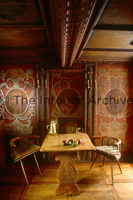In the dining room the ceiling is decorated with ornately carved beams and painted insets to match the panelled walls