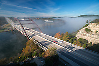 Traffic drives through the 360 Bridge is blanketed with fog during morning sunrise on a cold winter's morning on Lake Austin, Texas.