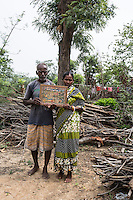 Meena Mahato (right), 60 years old, and her husband Shyanti Mahato, 67, live in the village of Bhaluk Pahari. 13 years ago, Meena was accused of being a witch after her son died. Despite a visit to the holy sanctuary of Goya (portrayed in the picture the couple hold in their hands) Meena and Shyanti were badly beaten, forced to leave their house and relocate at the edge of the village. Today, they are hosted by Shushen Mahato. The couple is barred from visiting the temple, the market or any social gathering within the village.