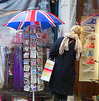 A woman stops against a Converse Shoes store to chat on her cell in Portobello Road, Notting Hill, London, UK. Picture by Manuel Cohen