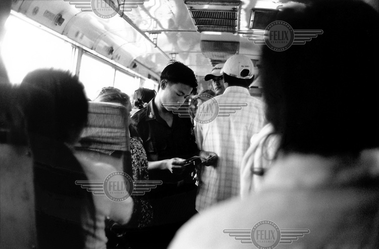 A soldier checks ID cards on a bus crossing from Mandalay Division to Shan State. After a series of bomb blasts in Rangoon and Mandalay, signs were erected by the junta at airports and at check points that read 'All Respect, All Suspect.'
