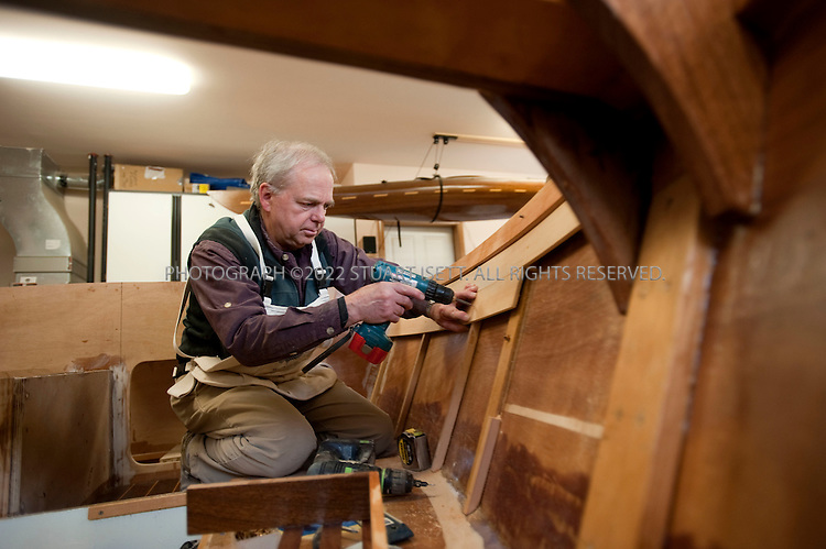 12/29/2009--Langley, WA, USA..Larry Cheek works in the garage of his home on Whidbey Island, WASH. on his latest wood boat, the 'Nil Desperandum'. The design is the Winter Wren II by Sam Devlin of Olympia, WA.and will be 18 feet long when completed...It's a gaff-rigged cruising sailboat made of plywood/fiberglass composite construction. The woods used are okoume plywood, khaya mahogany, white oak, and vertical-grain fir. Cheek started work on the boat in Oct. '08 and has a projected launch date of June '11. He estimates 1,500-2,000 hours of work will go into the boat...Here Mr. Cheek is trimming and installing thin fir planks on the inside of the hull to form the interior walls of the hull...©2009 Stuart Isett. All rights reserved.