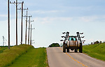 A tractor leaves a trail of mud on a rural road after spreading fertilizer on the fields in north central Illinois.