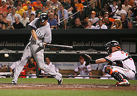 Michael Saunders #55 of the Seattle Mariners hits in front of Matt Weiters #32 of the Baltimore Orioles during a MLB game at Camden Yards, on August 8 2010, in Baltimore, Maryland. Orioles won 5-4 in extra innings.