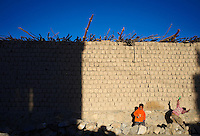 Two kids playing with plastic guns in front of a wall made of mud-bricks.<br />