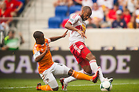 Corey Ashe (26) of the Houston Dynamo gets the back of Thierry Henry (14) of the New York Red Bulls leg as he goes for the ball. The New York Red Bulls defeated the Houston Dynamo 2-0 during a Major League Soccer (MLS) match at Red Bull Arena in Harrison, NJ, on June 30, 2013.