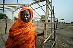 Angelina Methiang, a 42-year old refugee from the Nuba Mountains, poses with a house she is building in Abyei, a town at the center of the contested Abyei region along the border between Sudan and South Sudan. Methiang's home in the Nuba Mountains was destroyed in 2012 by troops from the Republic of Sudan, and she fled for the relative safety of Abyei, where in 2011 soldiers and militias from the northern Republic of Sudan had swept through the area, chasing out tens of thousands of residents and looting and burning what was left behind. Although Ethiopian peacekeepers patrol the region, renewed attacks in Abyei by northern-backed Misseriya militias in 2013 have Methiang and others worried. The African Union has proposed a new peace plan for Abyei, including a referendum to be held in October 2013, but it has been rejected by the Misseriya and Khartoum. The Catholic parish of Abyei, with support from Caritas South Sudan and other international church partners, has maintained its pastoral presence among the displaced and assisted them with food, shelter, and other relief supplies.