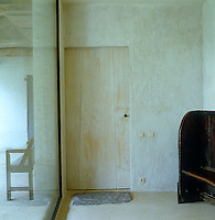 A contemporary glass wall and an ancient wooden door are interestingly juxtaposed in this hallway