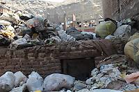 2011 Mokattam Garbage City (alla periferia del Cairo) il quartiere copto dove si vive in mezzo alla spazzatura raccolta: sacchi dell'immondizia in strada sopra ad un muretto. Sullo sfondo case nuove in costruzione sul fianco della montagna.