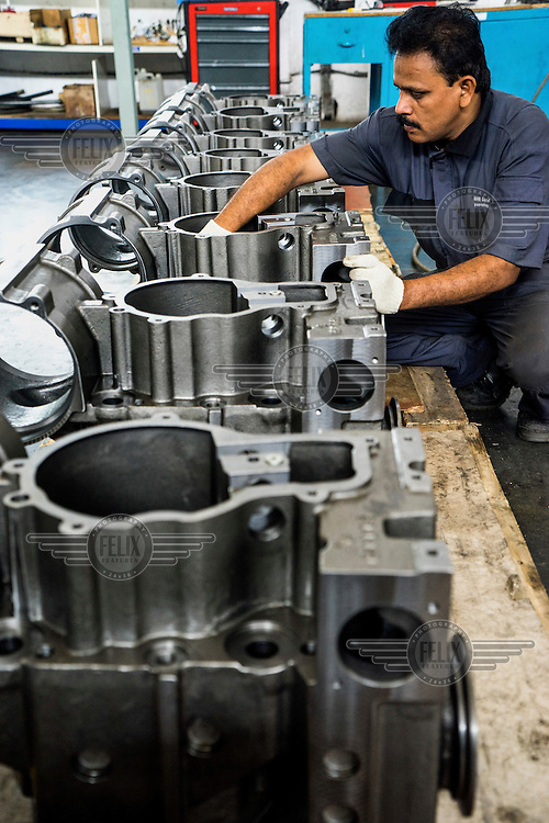 Staff, on the factory floor, working on diesel engines at the MAN diesel and turbo factory.