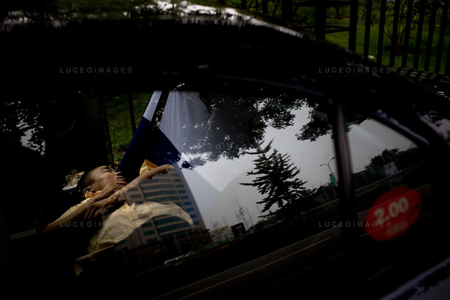 A taxi driver takes an afternoon nap in downtown Beijing, China on Wednesday, August 13, 2008.  Kevin German