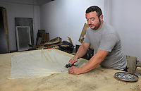 Nacho is stretching and fixing a skin on a wooden sheet for the drying process at the tannery factory of Scriptorium SL in Valencia, Spain. Picture by Manuel Cohen