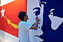 A man paints a murales with the NLD flag and a stylized image of Aung San Suu Kyi..Yangon, Myanmar. 2012