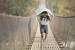 Rebuilding supplies are carried by hand across a suspension bridge into Adamtar, an indigenous village in Nepal's Dhading District where Dan Church Aid, a member of the ACT Alliance, is helping families to rebuild their homes and lives in the wake of the 2015 earthquake that ravaged much of Nepal.
