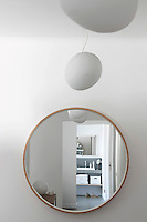 The ensuite bathroom is reflected in a circular mirror on the wall of the master bedroom