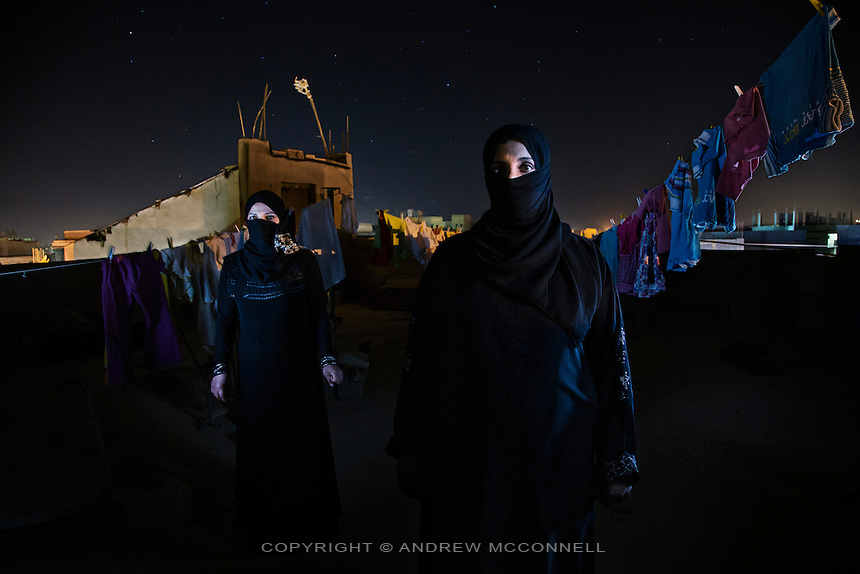 Syrian refugees, Ihsan, 28, and her cousin, Sammia (left), pictured on a rooftop in Al Mafraq, Jordan. They had crossed the border into northern Jordan 3 days earlier after fleeing the increasing violence in Syria.<br /> <br /> Words of Ihsan: &quot;We left our house 3 months ago because there was a lot of shooting and bombing in our area. We went to the grasslands around Homs and moved from place to place. We had a tent and moved 6 or 7 times, drinking water from the springs and receiving food from the local people. My family contains 8 people and  we traveled with 4 other families, we were always afraid of the army finding us. <br /> <br /> After 15 days I returned to my house to get clothes for the children and found everything there destroyed. There were soldiers everywhere in the streets around my house. Two huge men stopped me and pointed their guns at me and questioned me about my husband; I said he was dead. When I got to my house it was destroyed, one side was missing and everything was stolen. The men had followed me and when I left I was shot at, a bullet went past my ear and I ran. I saw many dead bodies on the street, men, women, and children. <br /> <br /> We decided to move to Jordan because the situation was becoming very bad in the country. We moved south from place to place sometimes walking and sometimes by bus. We slept in the open or if it was cold we pitched our tent, when we got to Deraa the Free Syrian Army helped us to cross the border. There was a crowd of around 90 people and we walked together across the countryside and sometimes when the Syrian Army spotlight was shining we had to duck. We gave the children medicine so they would sleep and not make noise. I am 7 months pregnant but I wasn't worried about my baby because I am used to being in this situation. I have been in Jordan for 3 days and I feel safe and calm, there are no sounds of bullets or bombs&quot;.