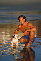 Young man and his dog posing for a picture together on the wet sands of the beach